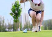 Fotografie Golfspielerin hält Golfball auf hölzernem Abschlag auf T-off, bereitet sich vor und ist bereit, den Ball zum Zielpunkt im Fairway zu schlagen