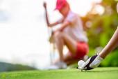 Hand einer jungen Golfspielerin, die den Golfball auf einem hölzernen Abschlag liegend hält, vorbereitet und bereit, den Ball zum Ziel zu schlagen, Konkurrent oder Golfkumpel im Hintergrund zuschauend