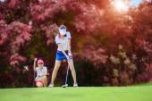 Fotografie junge Golfspielerin in Aktion beim Setup Adresse, um den Golfball vom T-off auf das Ziel grüne Fairway zu schlagen, konzentrieren Setup Adresse, um den Ball wegzuschlagen