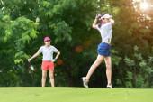 Golferin in Aktion beim Aufbau, um den Golfball vom T-off zum Zielgrün zu schlagen, Fairway bei hellem Himmel, Par 3 schlägt den Ball