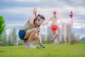 Fotografie junge Golfspielerin platziert einen Ball auf dem Grün, um zum Zielpunktzahl zu putten, konzentriert sich, um die Linie des Puttens zu lernen, um die Gewinnpunktzahl zu erreichen
