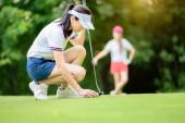 Golfspielerin nimmt Golfball, der auf dem Grün zum Putten auf das Loch im Golfschläger liegt, Gegner oder Konkurrent beobachtet oder wartet im Hintergrund