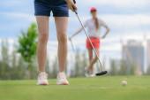 Fotografie junge Golfspielerin wirft Golfball in das Loch auf dem Grün des Golfplatzes, ein Gegner oder Konkurrent wartet im Hintergrund