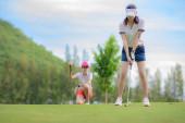 Fotografie Golferin in Aktion beim Setup für den Rückschwung, um den Golfball vom T-Off zum Ziel auf dem Grün zu schlagen, Fairway bei hellem Himmel, Par 3 t off