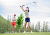 Golferin in Aktion beim Setup des Rückschwungs, um den Golfball vom T-Off zum Ziel auf dem Grün zu schlagen, Fairway bei hellem Himmel, Par 3 t off