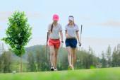 junge asiatische Golfspielerinnen, die zusammen auf dem Grün gehen, genießen das Golfspiel Wettbewerber im Fairway, golfmate spielen zusammen Glück