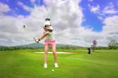 Golferin in Aktion beim Aufbau, um den Golfball vom rauen Fairway zum Zielgrün zu schlagen, Fairway bei Tageslicht