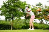 Fotografie Golfspielerin in Aktion, wenn sie den Golfball vom rauen Fairway zum Zielgrün schlägt