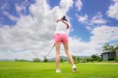 Fotografie Rückseite der Golfspielerin konzentrieren sich auf den Schlag oder chippen den Golfball weg zum Zielgrün, um bei der Trefferquote zu gewinnen