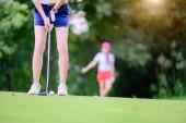 Hand einer jungen Golfspielerin, die den Putter hält, um den Golfball zum Ziel des Golfspiels zu schlagen, hält den Golfball auf dem Grün, im Hintergrund beobachtet ein Mitspieler oder Golfspieler