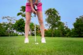 Fotografie Golfball wird von Golferin vom Rough des Fairways auf das Grün gechipt, um Endstand zu erzielen