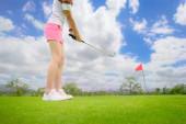 Golfspielerin konzentriert sich beim Schlag des Golfballs auf das Zielgrün für den Sieg bei der Punktzahl