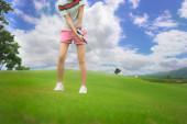 Fotografie Golferin in Aktion schlug Golfball bei Tageslicht von Fairway auf Zielgrün