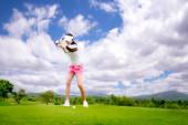 Fotografie Golferin in Aktion beim Setup der Adresse, nachdem sie den Golfball vom Fairway weg zum Zielgrün geschlagen hat, Fairway bei Tageslicht