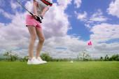 Fotografie Golfspielerin in Aktion als Chip-Golfball vom rauen Fairway zum Zielgrün bei Tageslicht