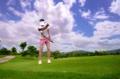 Golfspielerin in Aktion, als Chip-Golfball vom rauen Fairway bis zum Zielgrün bei Tageslicht.