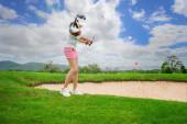 Fotografie Golfspielerin in Aktion, die nach einem Schlag oder Chip einen Golfball von der rauen Spielbahn auf das Zielgrün bei Tageslicht setzt.