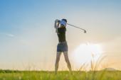 Fotografie Golferin in Aktion beim Aufbau, um den Golfball vom Fairway weg zum Zielgrün zu schlagen, Fairway bei Sonnenuntergang