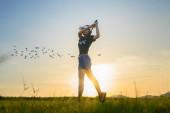 Fotografie Golferin in Aktion beim Setup, nachdem sie den Golfball vom Fairway weg zum Zielgrün geschlagen hat, Fairway bei Sonnenuntergang