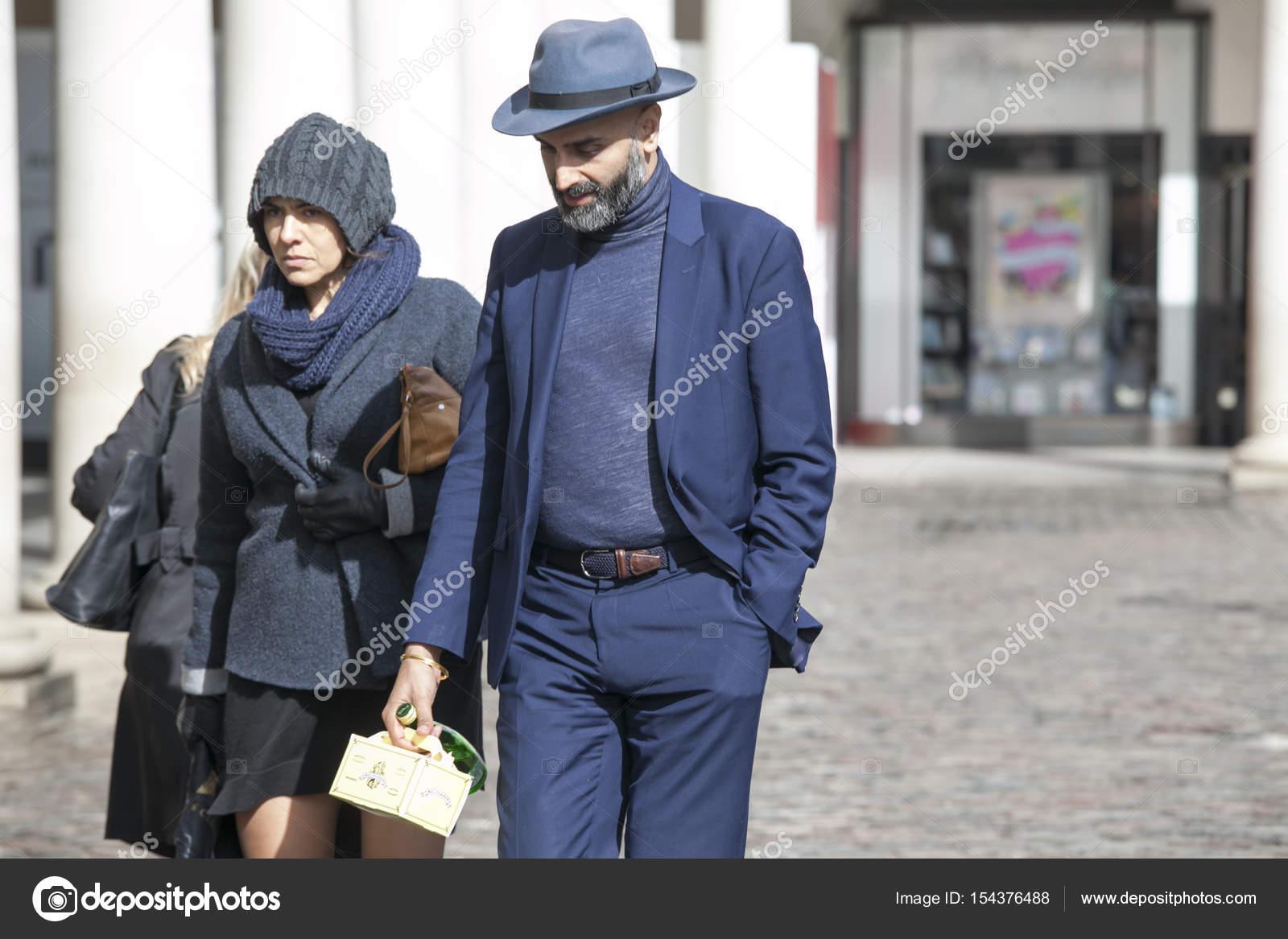 5e11057fd17ef Vestiti alla moda uomo e donna in vestiti blu e cappelli cammina per ...