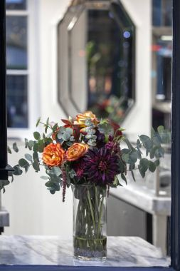 the Bouquet of orange roses, purple dahlias and eucalyptus in a glass vase in front of a mirror
