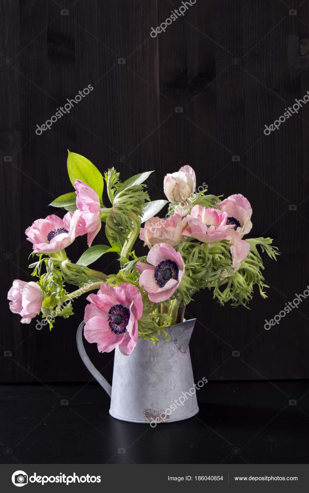 The wedding bouquet of anemones with ruscus in a jug on a black the wedding bouquet of anemones with ruscus in a jug on a black background stock izmirmasajfo