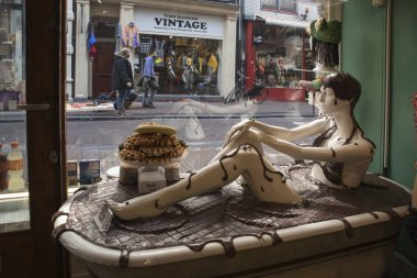 Showcase of a chocolate shop with a bath inside. In the chocolate bath sits a mannequin in a swimsuit made of chocolate