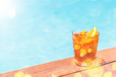 Negroni cocktail near a pool at the resort bar or suite patio. Luxury resort, vacation, room service concept