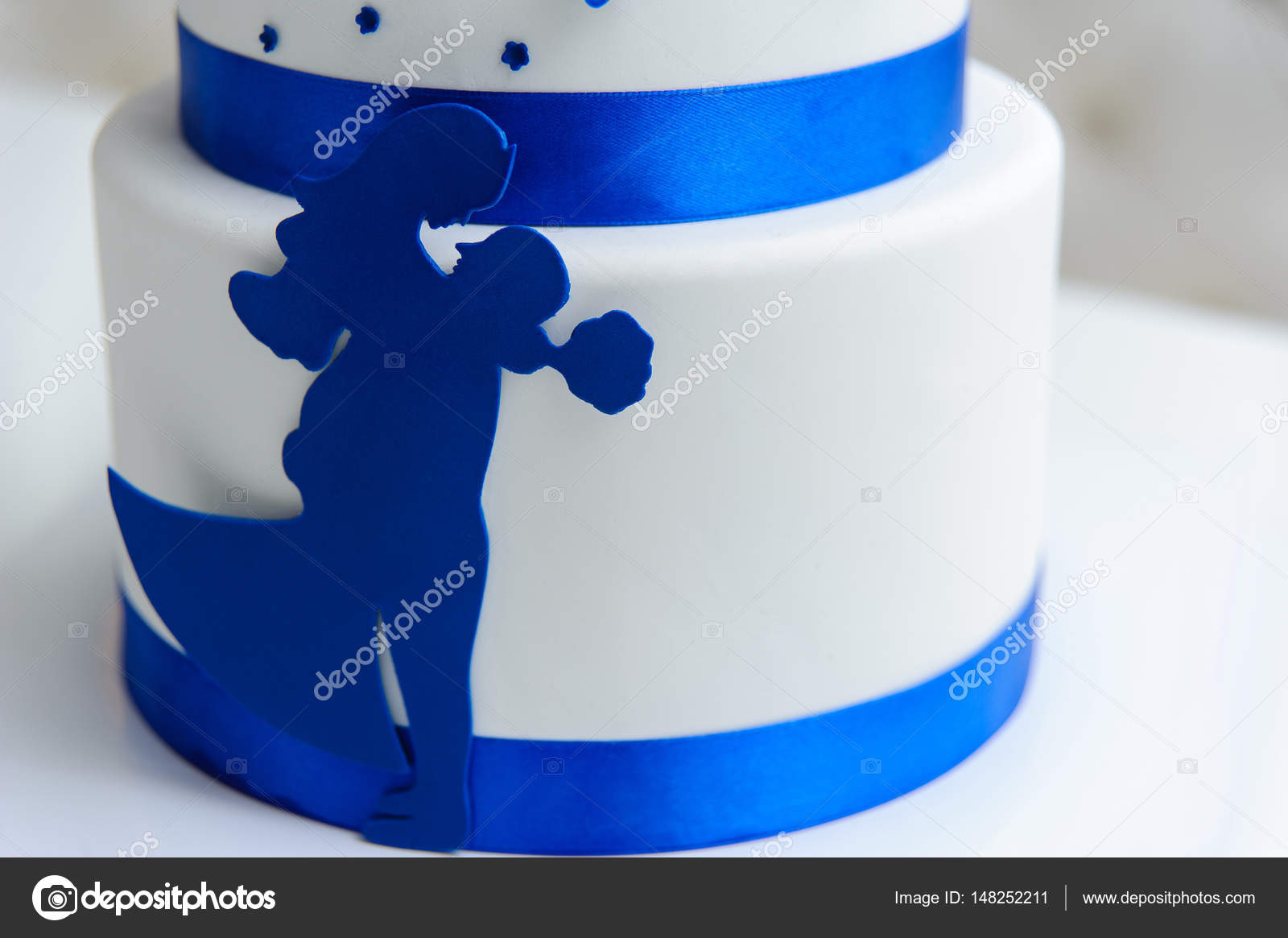 White wedding cake with blue flowers and a bow also with the fi white wedding cake with blue flowers and a bow also with the fi stock izmirmasajfo Images