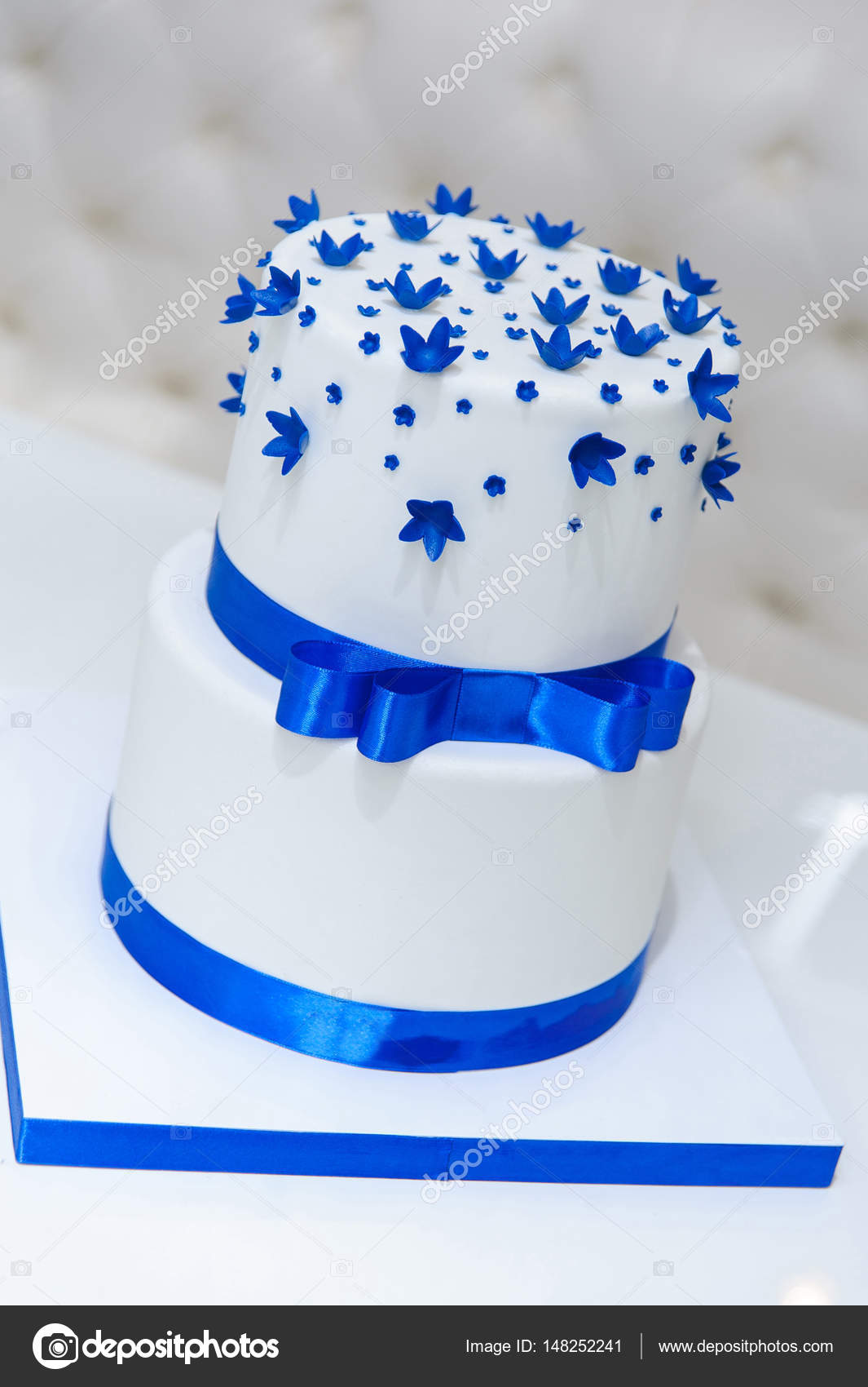 White wedding cake with blue flowers and a bow stock photo white wedding cake with blue flowers and a bow stock photo izmirmasajfo