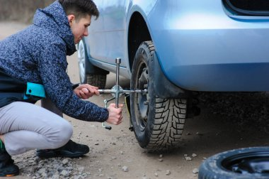 A man broke a wheel on a car and changes it on his own on the ro