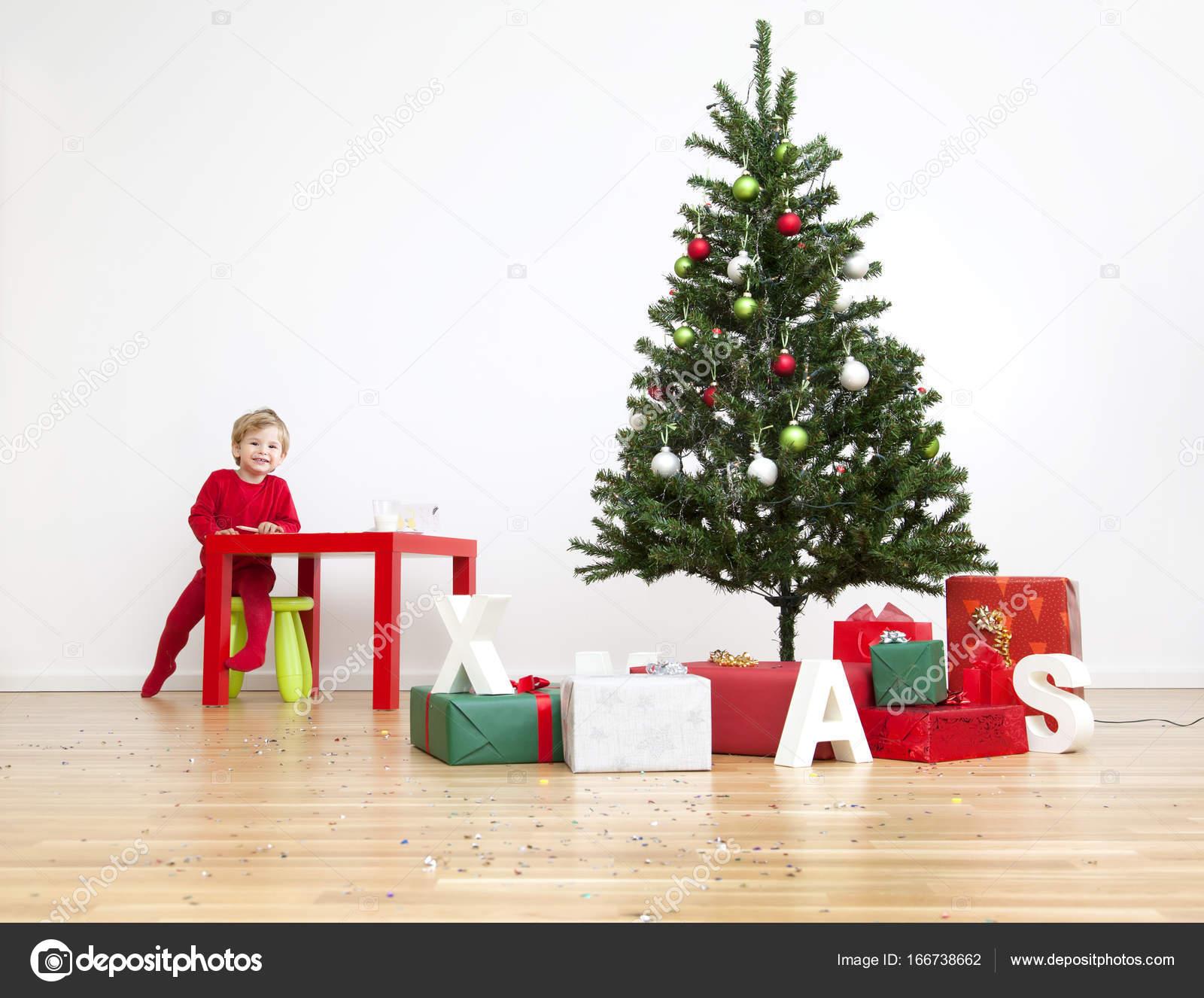 Alberi Di Natale In Legno Da Parete : Bambino di natale felice con i regali e lalbero nella sua casa