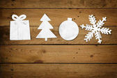 Christmas Paper Ornaments, Merry Christmas on a wood table background: Cute little paper cut outs of christmas decoration items, Gift, Tree, Bauble and Snowflake