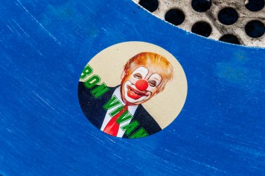 Nice, France - March 8, 2020: a sticker with Donald Trump in clown makeup found on a trash can
