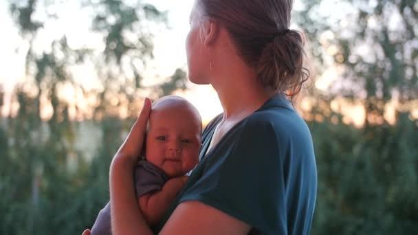 Bambino sveglio sul petto di madri. Donna vaga guardando il tramonto