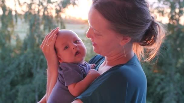 Donna caucasica con un bambino a tempo di tramonto. Colpo palmare