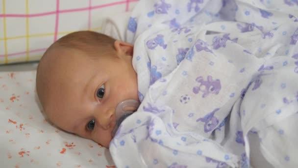 Newborn baby falling asleep in a cradle. Handheld shot