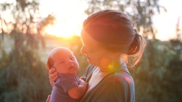 Giovane madre con un bambino in braccio a raggi del sole di regolazione. Colpo palmare