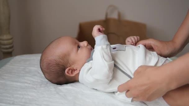 Mani femminili abbigliamento un bambino sveglio in pannolino. Colpo palmare
