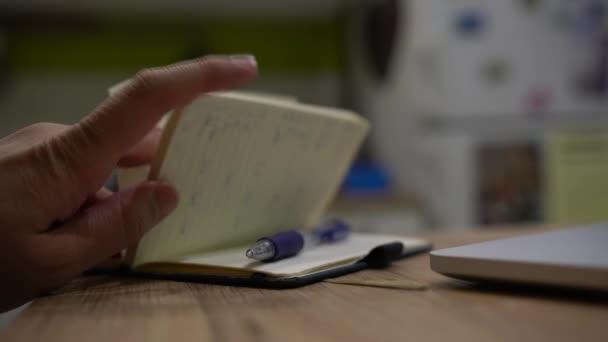A férfi keze jegyzetfüzet megnyitása és a tollal írás közelről