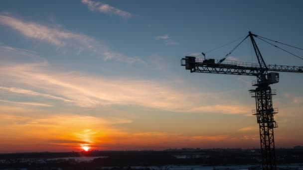 Timelapse with crane working on construction site on sunset sky background