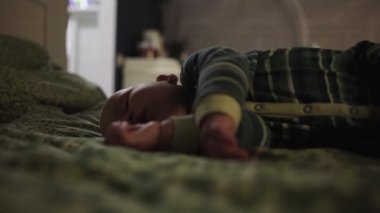 Adult covers sleeping baby with knitted plaid