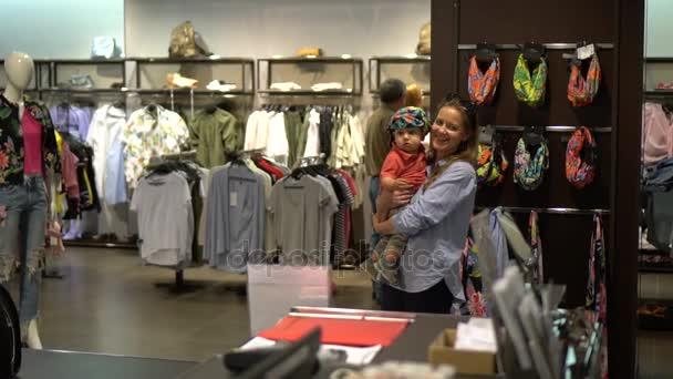 Směje se žena s dítětem během nakupování oblečení v obchodě. Kapesní zpomalený záběr