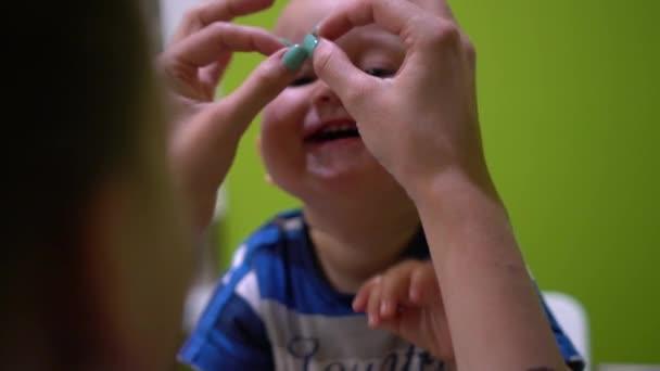 Giochi della madre con il bambino felice che fa maschera dalle mani. Palmare movimento basso girato