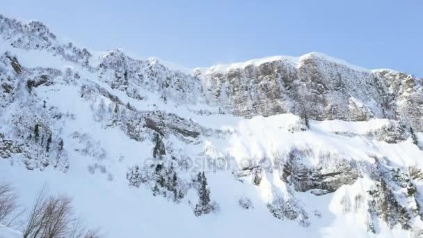 Meredek hegygerinc hóval. Napos sziklás lejtőn. Krasnaya Polyana, Kaukázus, Oroszország
