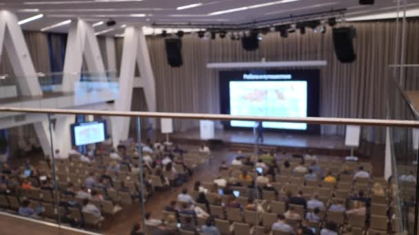 Přednášející z jevištní přednášky pro diváky ve velkém pokoji s řadami sedadel. Rozostřený