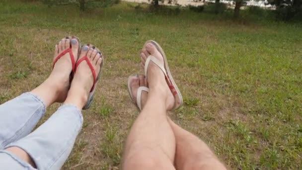 Muž a žena v žabkách na houpačce. Pohled na mužské a ženské nohy