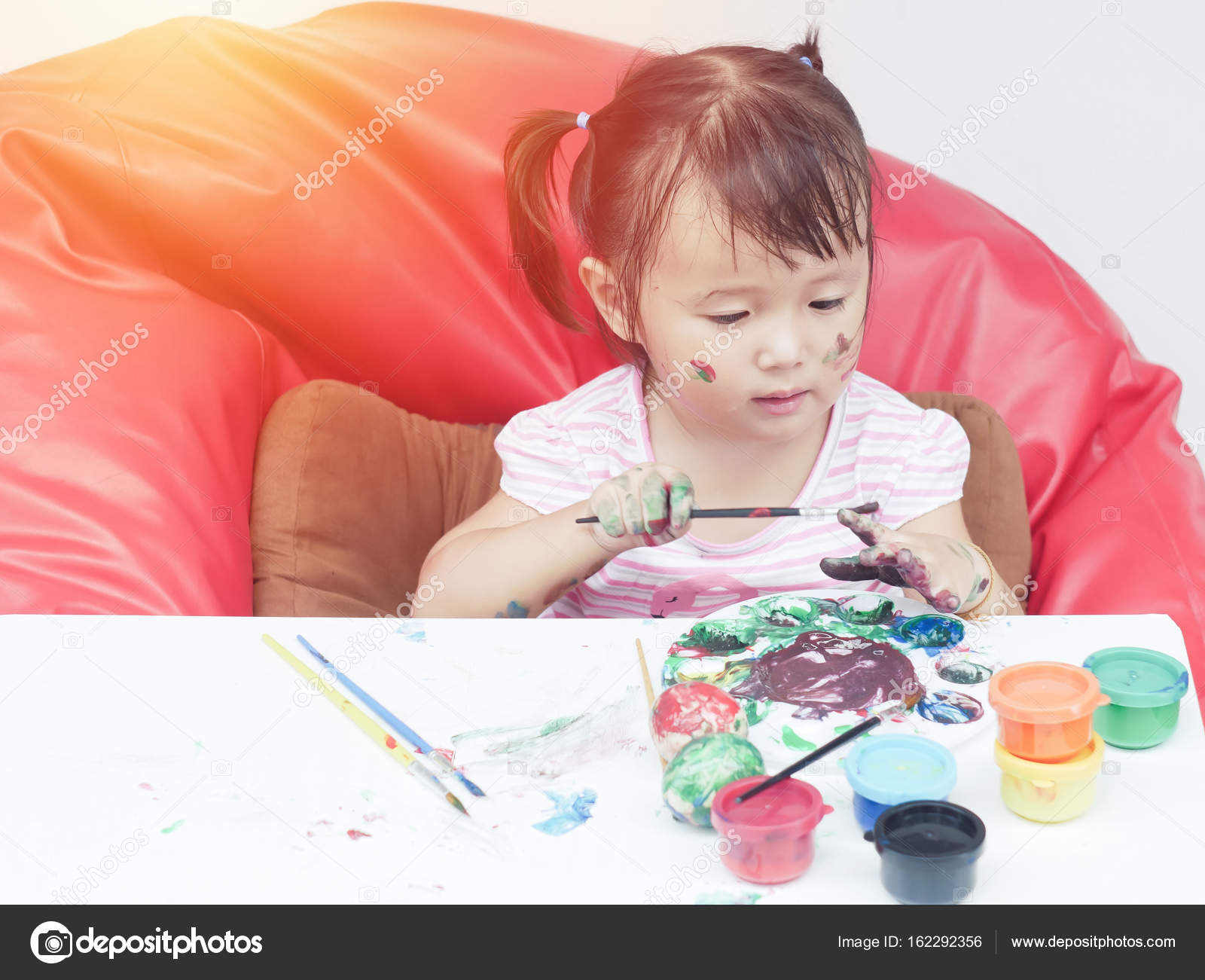Kleine Mädchen-Malerei mit Pinsel und bunten Farben von Finger Hand ...