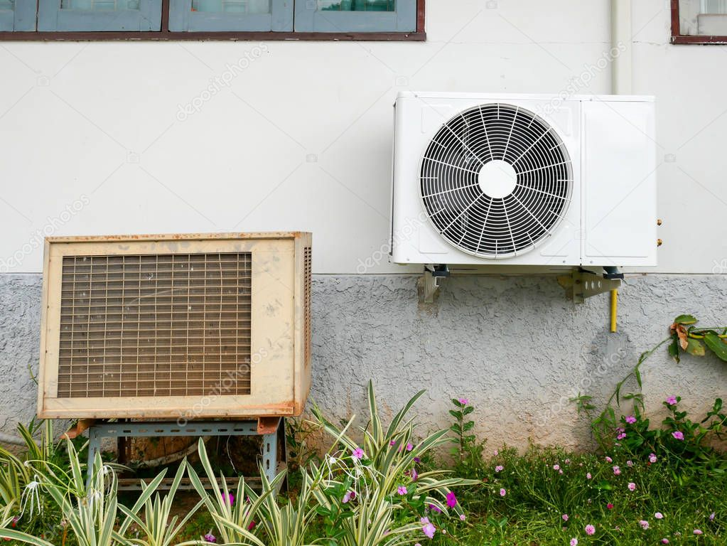 new air conditioner condenser and old air conditioner condenser unit standing outdoors