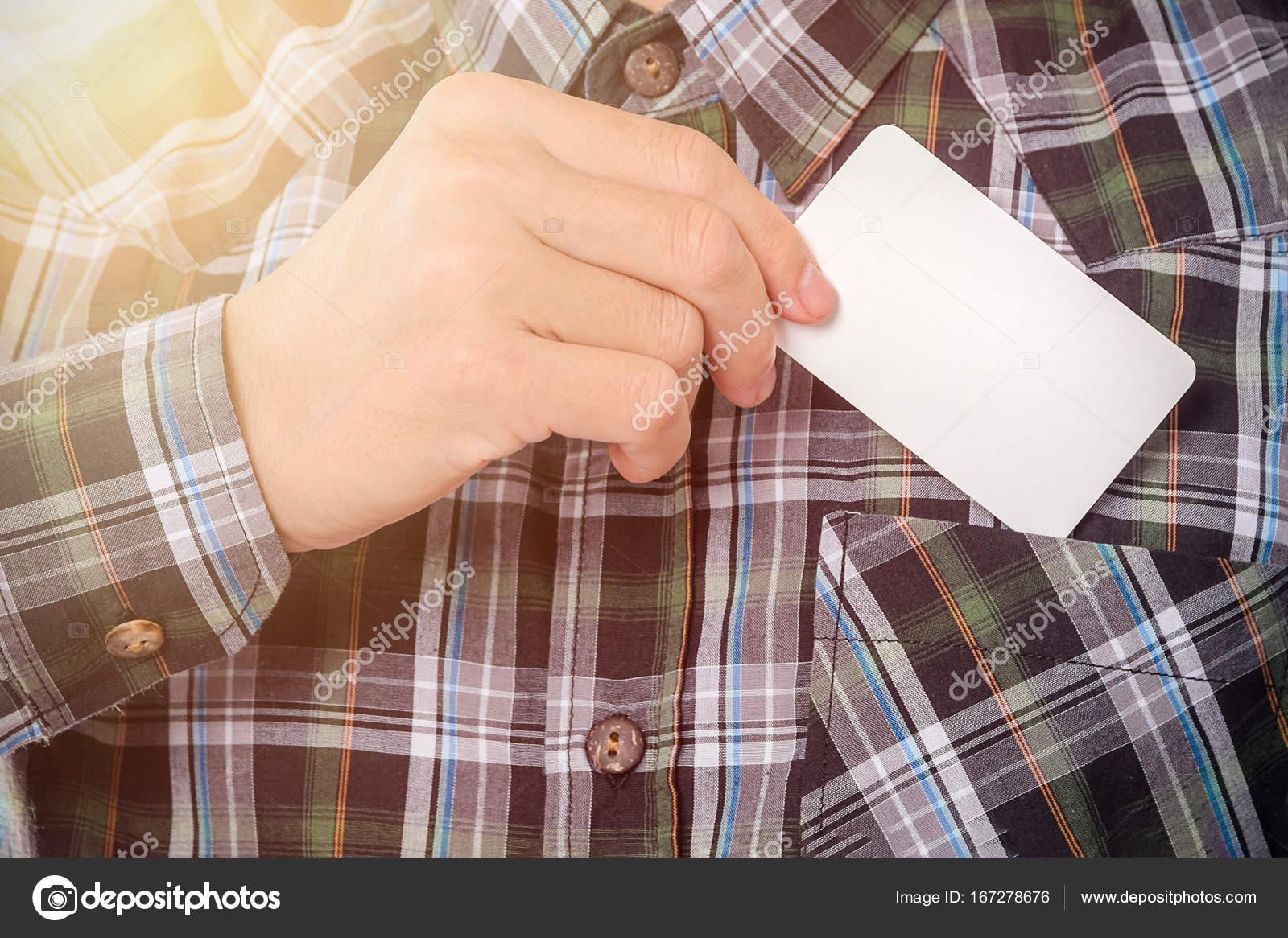 Joven saca en blanco tarjeta de visita del bolsillo de su camisa ...